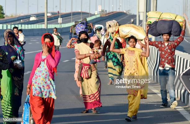 A group of migrant workers and families from Madhya Pradesh walk along National Highway 24 to Sarai Kale Khan Bus stand in search of any bus for...