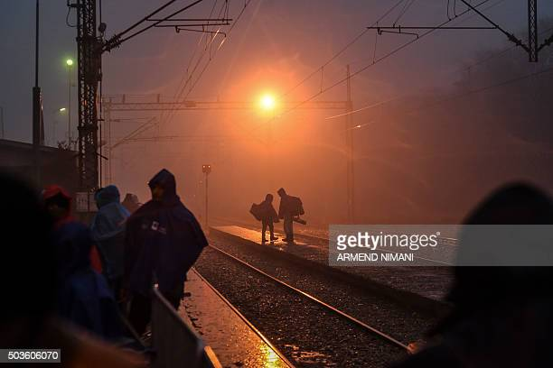 A group of migrants and refugees wait at a train station for a train in southern Serbian town of Presevo on January 6 2016 The International...
