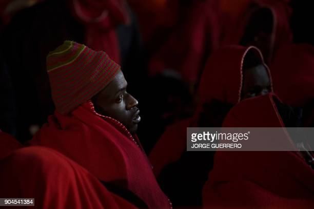 A group of migrants arrive on board a Spanish coast guard vessel at the southern Spanish port of Malaga on January 13 2018 following the rescue of an...