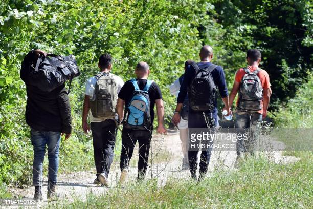 A group of migrants from the Asian continent walk on a dusty track through a wooded area in the countryside near Bosanska Krupa in Northern Bosnia on...