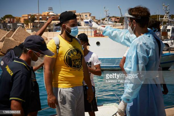 Group of migrants from Tunisia are checked by the medical staff as they get of a boat on August 28, 2020 in Lampedusa, Italy. Lampedusa, which is at...