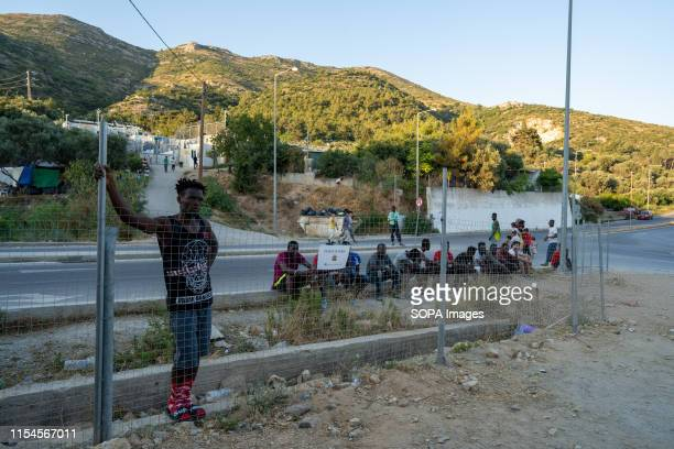A group of migrants living in or around the migrant camp on Samos gather to watch a game of football between players from Cameroon and the Democratic...