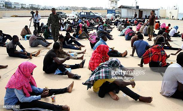 A group of migrants mostly Africans attempting to reach Europe rescued by the Libyan coastguard at sea wait in a naval base near the Libyan capital...