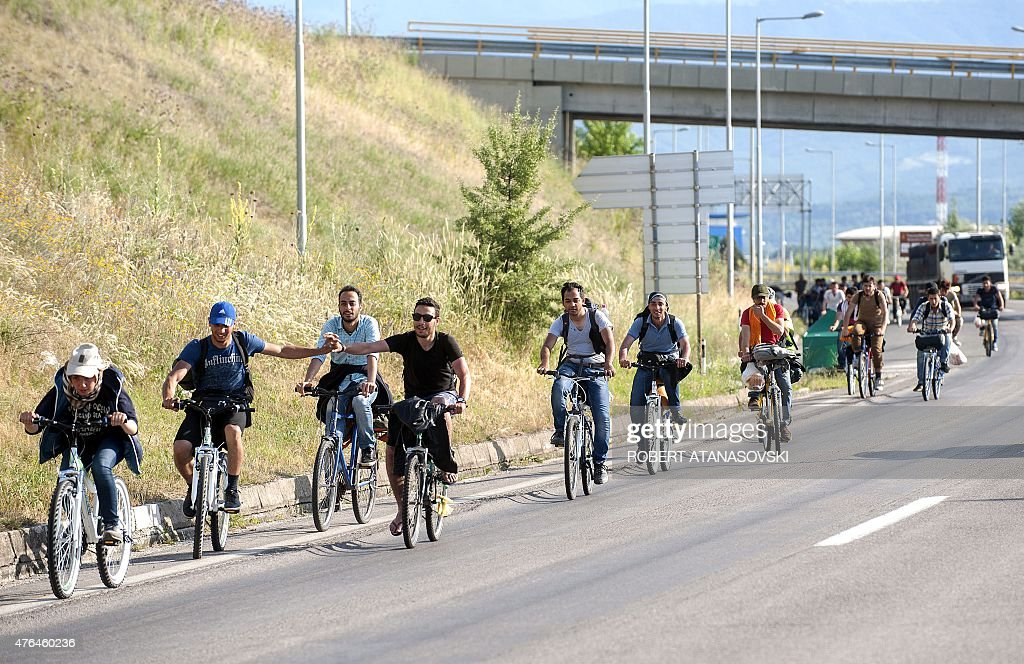 A group of migrants ride bicycles on a highway near the town of Veles on June 9, 2015. Migrants from impoverished and war-torn countries in Africa, the Middle East and central and south Asia walk through Macedonia along the line to reach Serbia as they head north from Greece in the hope of crossing the European Union border into Romania, Hungary and Croatia. AFP PHOTO / ROBERT