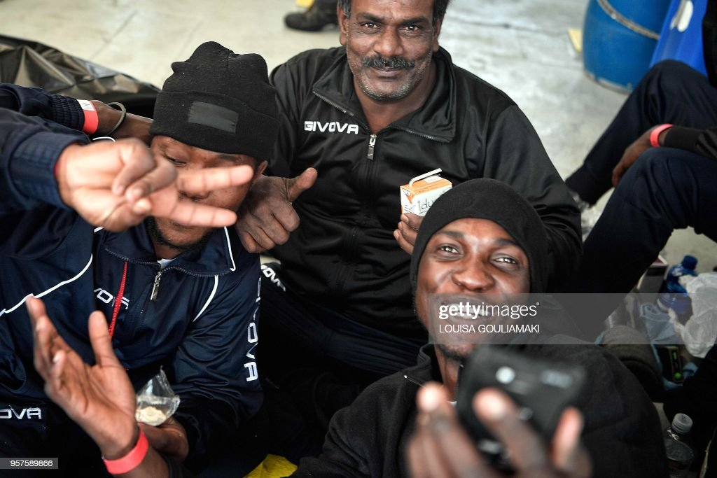 group-of-migrants-take-selfies-aboard-mv-aquarius-just-after-being-picture-id957589866