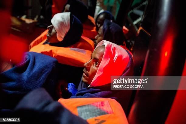 A group of migrants wait to be transferred from the Spanish war ship Santa Maria to the nongovernmental organization Aquarius ship by SOS...