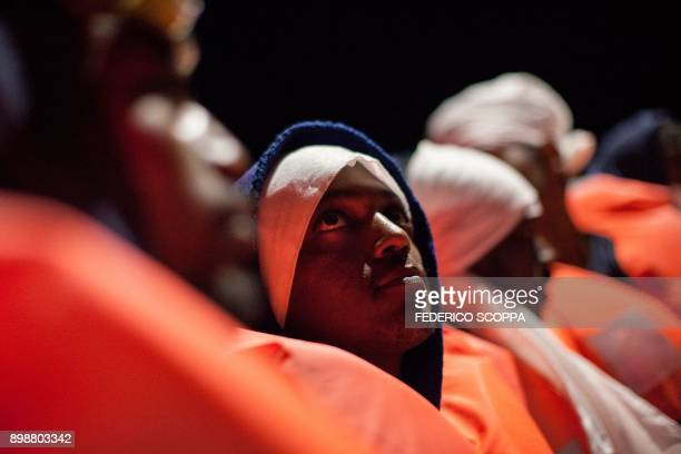 TOPSHOT A group of migrants wait to be transferred from the Spanish war ship Santa Maria to the nongovernmental organization Aquarius ship by SOS...