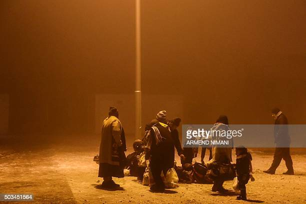 TOPSHOT A group of migrants wait to board a bus in Presevo southern Serbia on January 5 2016 The United Nations refugee agency and the International...