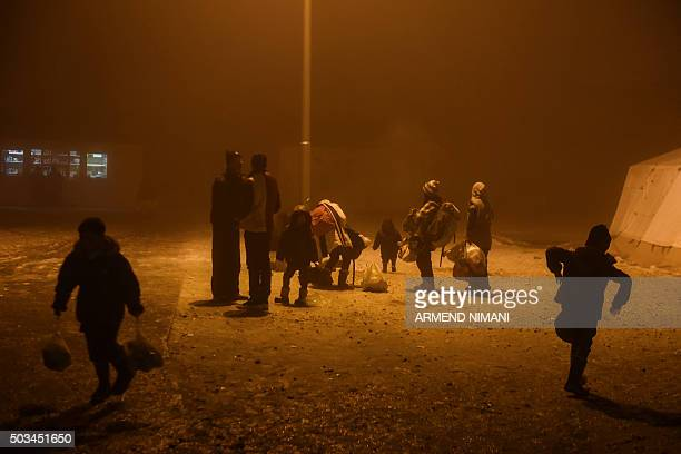 A group of migrants wait to board a bus in Presevo southern Serbia on January 5 2016 The United Nations refugee agency and the International...