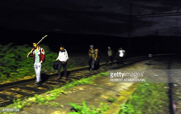 A group of migrants walk on the railroad tracks on May 4 near the town of Veles in central part of Macedonia as migrants from impoverished and...