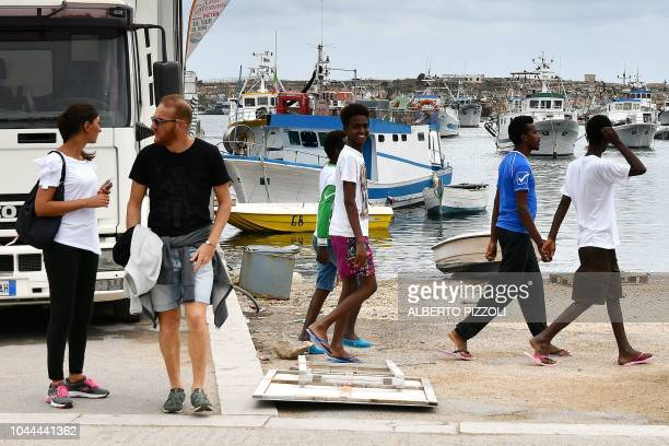 A group of migrants who recently arrived from Eritrea through Libya walk past tourists in the harbour of Lampedusa on September 26 2018 Five years...