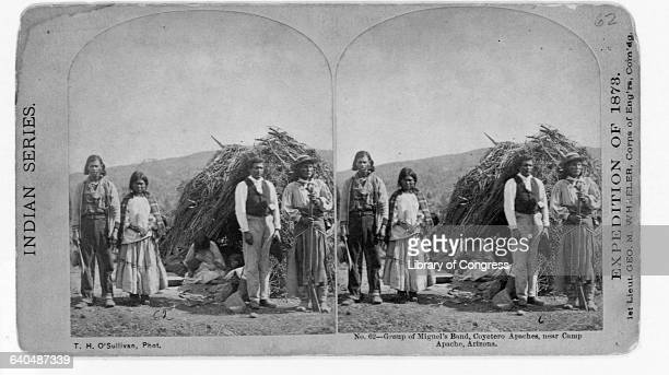 A group of Miguel's Band Coyetero Apaches standing in front of their wickiup with woman sitting on ground breast feeding her baby near Camp Apache...