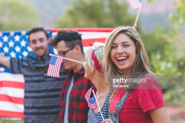 group of millennial friends hold a large american flag - fourth of july stock pictures, royalty-free photos & images