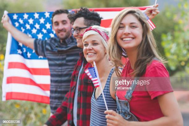 group of millennial friends hold a large american flag - fourth of july stock photos and pictures