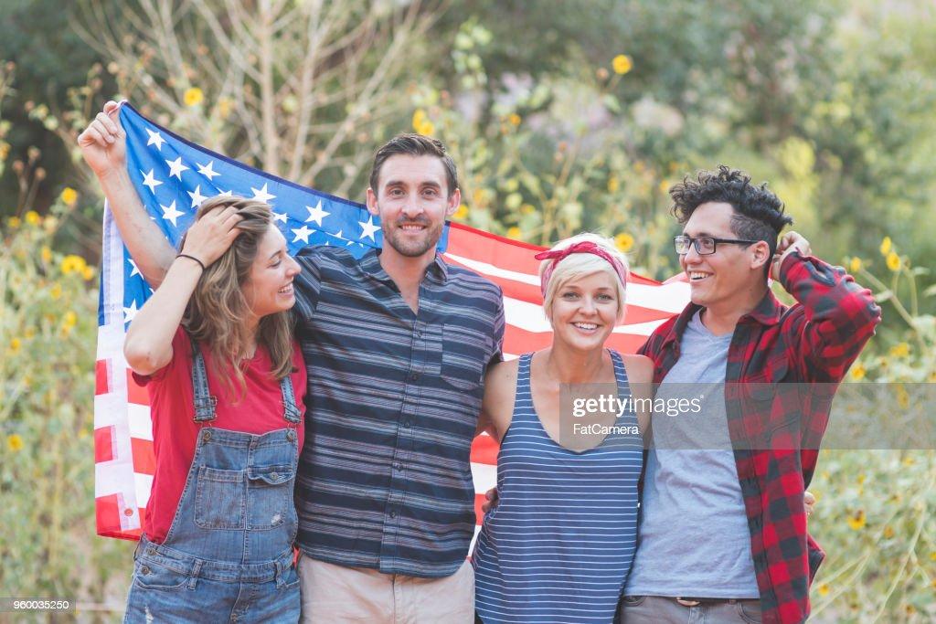 Gruppe von tausendjährigen Freunden halten eine große amerikanische Flagge : Stock-Foto