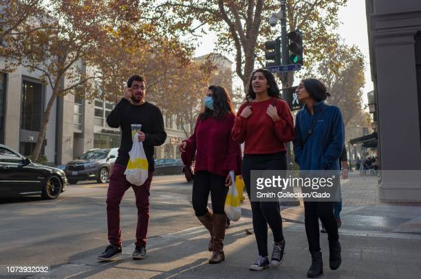 Group of Millennial generation friends holds takeout food bags and walks down University Avenue in the Silicon Valley, Palo Alto, California, with...