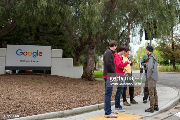 A group of millennialage young male technology workers stand in a group near signage for Google Inc at the Googleplex the Silicon Valley headquarters...