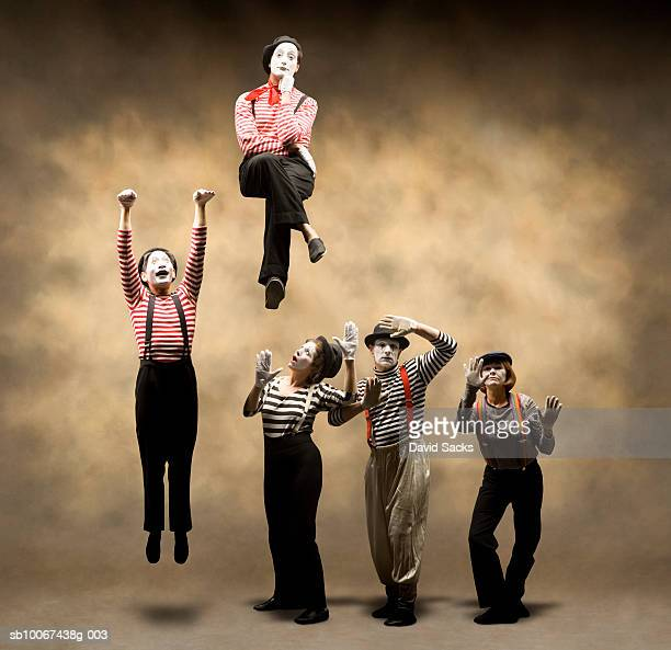Group of mimes stuck behind wall, one hanging, another sitting on top