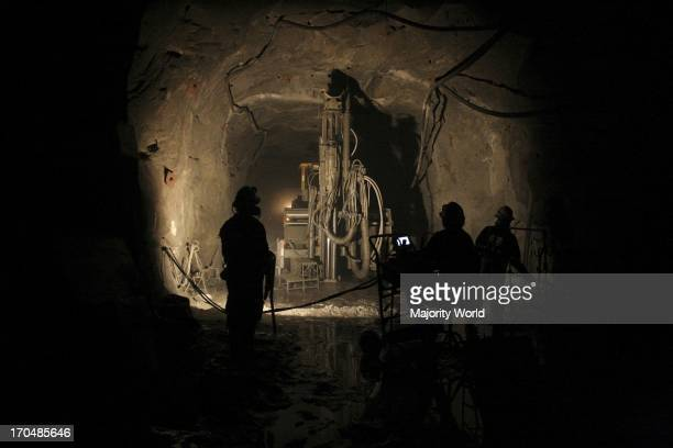 A group of miners are drilling a mine with the help of a completely mechanized drilling system inside a mine Chincha Ica Peru January 2008