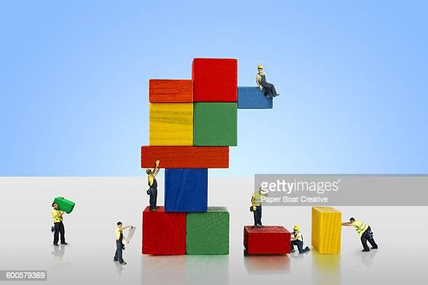 group of miniature men fixing giant building block