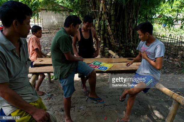 MAJULI JORHAT ASSAM INDIA A group of Mishing boys play a game of ludo at their village in Jorhat The Mishings are the largest ethnic tribal community...