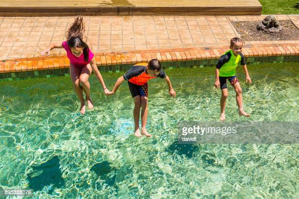 Group of Mixed Race Children Jumping in a Swimming Pool
