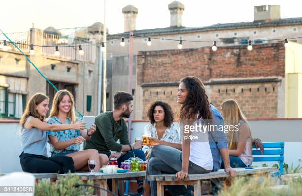 Group of mixed race young people, friens, together on a rooftop party
