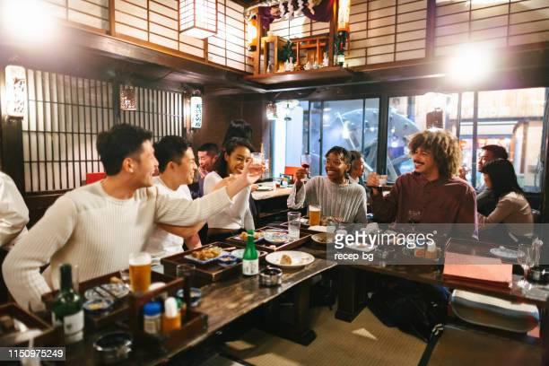 日本式パブでアルコールを楽しむミックスレース旅行者のグループ - 混血 ストックフォトと画像