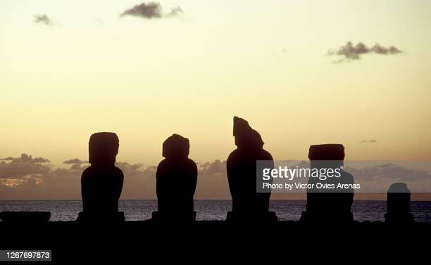 group of moais (monolithic human figures) back-lit at sunset on easter island - victor ovies fotografías e imágenes de stock