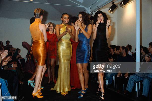 A group of models applaud Tunisian designer Azzedine Alaia at his 1986 springsummer women's fashion show in Paris The models are wearing colorful...