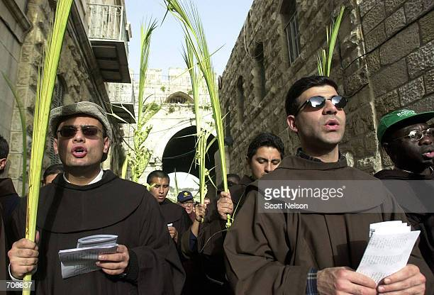 A group of monks sing songs and wave palm fronds in Jerusalem March 24 2002 as they celebrate Palm Sunday by retracing the steps of Jesus Christs...
