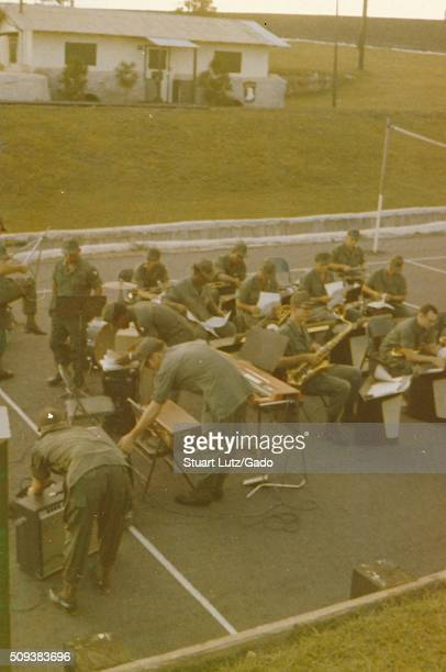 A group of more than a dozen soldiers members of the 101st Airborne Division sets up to perform as a band consisting of brass instruments drums and...