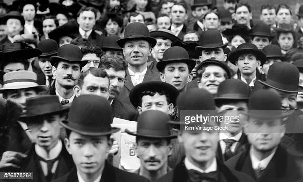 A group of mostly men with bowler hats on crowds together