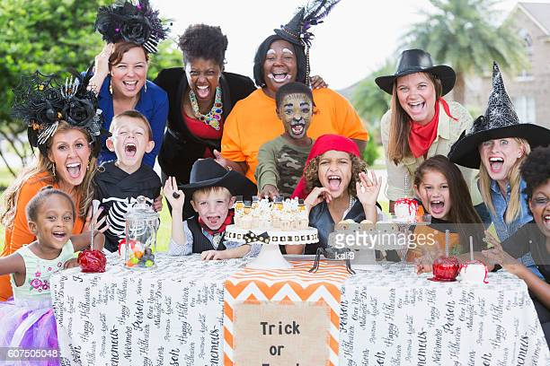 group of mothers and children at halloween party - halloween party stock photos and pictures