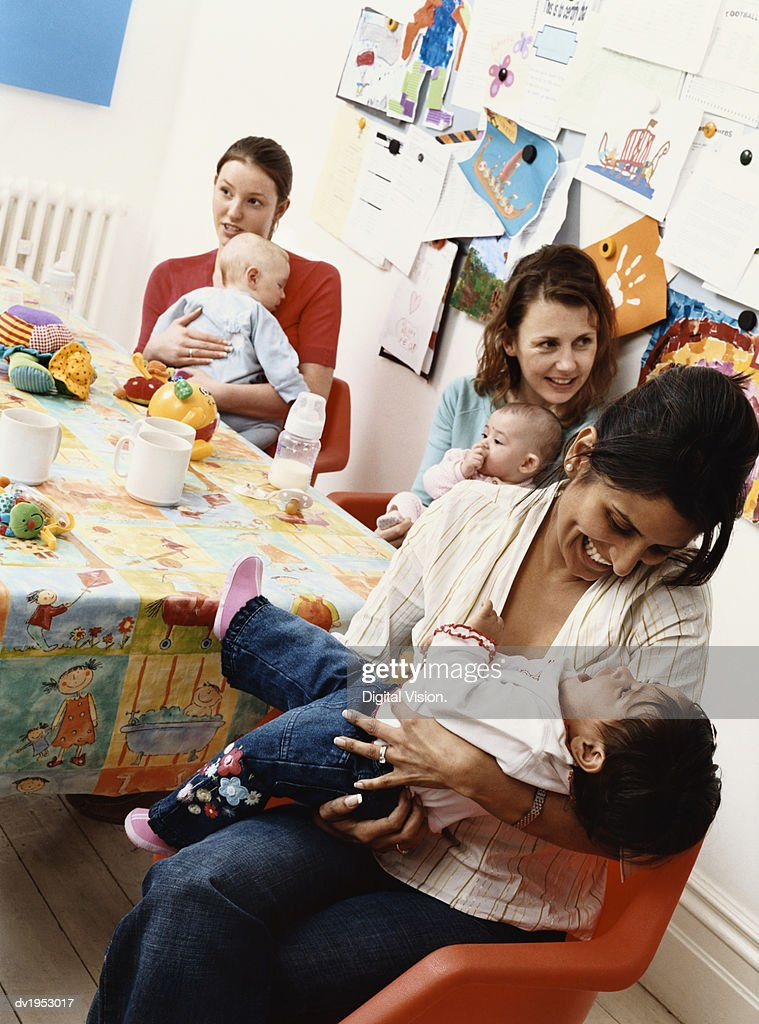Group of Mothers and Their Babies Sitting Around a Table : Stock Photo