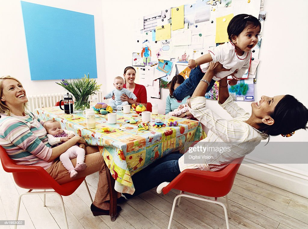 Group of Mothers and Their Offspring Sitting Around a Table : Stock Photo