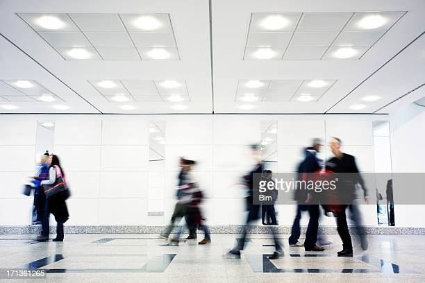 group of motion blurred people walking through illuminated corridor - ceiling stock pictures, royalty-free photos & images