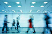 Group of Motion Blurred People Walking Through Illuminated Corridor