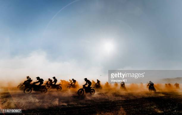 group of motocross motorcycles coming out in the race - モータースポーツ ストックフォトと画像