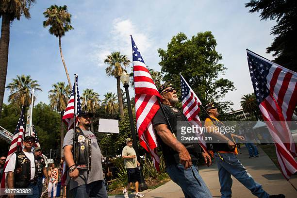 A group of motorcyclists march while holding American flags before a parade honoring Alek Skarlatos Anthony Sadler and Spencer Stone for their August...