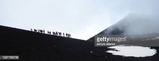 A group of mounatineers and tourists are pictures on the summit of Mount Etna near Catania on Sicily Italy 09 May 2013 Mount Etna with a height of...