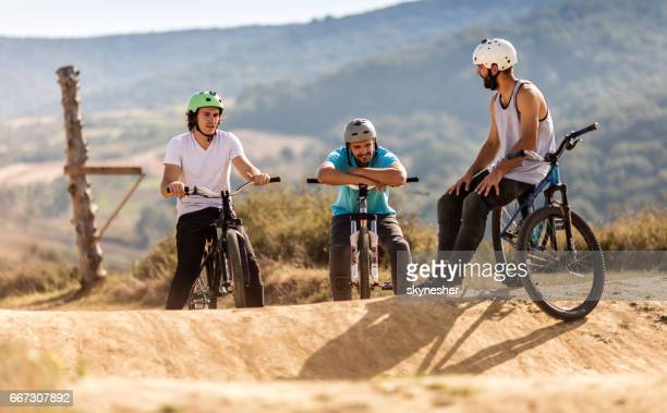 Group of mountain bike cyclists relaxing on dirt road.
