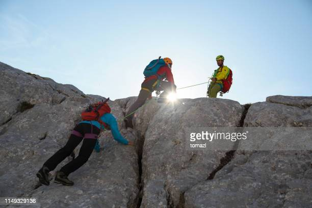 group of mountain climbers on their way to the top - messa in sicurezza foto e immagini stock