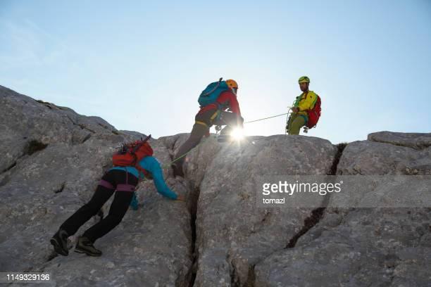 bergsteigergruppe auf dem weg nach oben - klettern stock-fotos und bilder