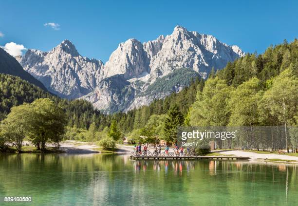 group of mountainbikers at jasna lake, slovenia. - slovenia stock pictures, royalty-free photos & images