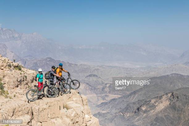 group of mountainbikers posing at hajar mountains, oman. - muscat governorate stock pictures, royalty-free photos & images