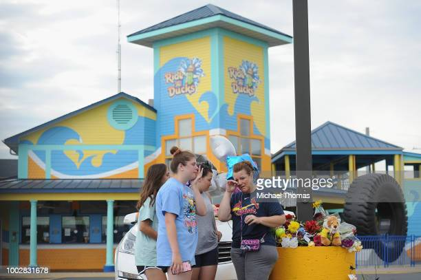 A group of mourners pause for a moment of prayer at Ride The Ducks Tours on July 20 2018 in Branson Missouri Hundreds of mourners stopped by the...
