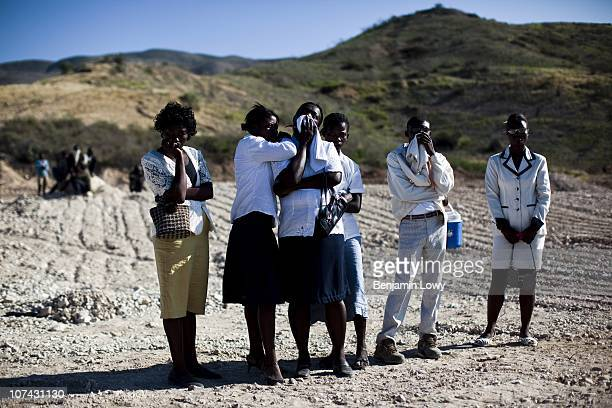 Group of mourners stand on top of a mass grave housing over 100,000 victims of the Haitian earthquake located on the outskirts of Port au Prince in...