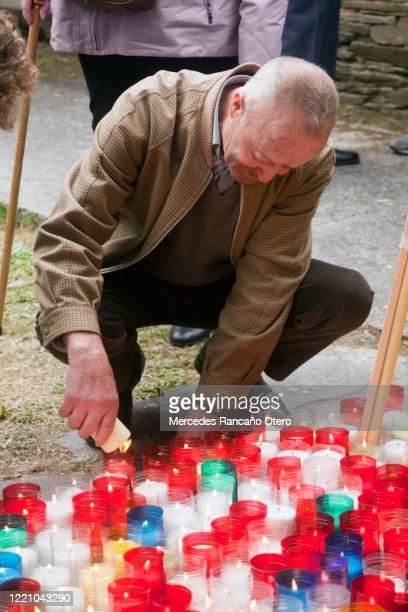 多色の奉納キャンドルのグループは、それらの1つを点灯シニアの男。 - 復活徹夜祭 ストックフォトと画像