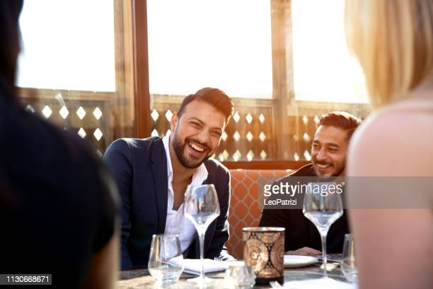 group of multi ethnic arab friends lunch in a restaurant in dubai - dining stock pictures, royalty-free photos & images